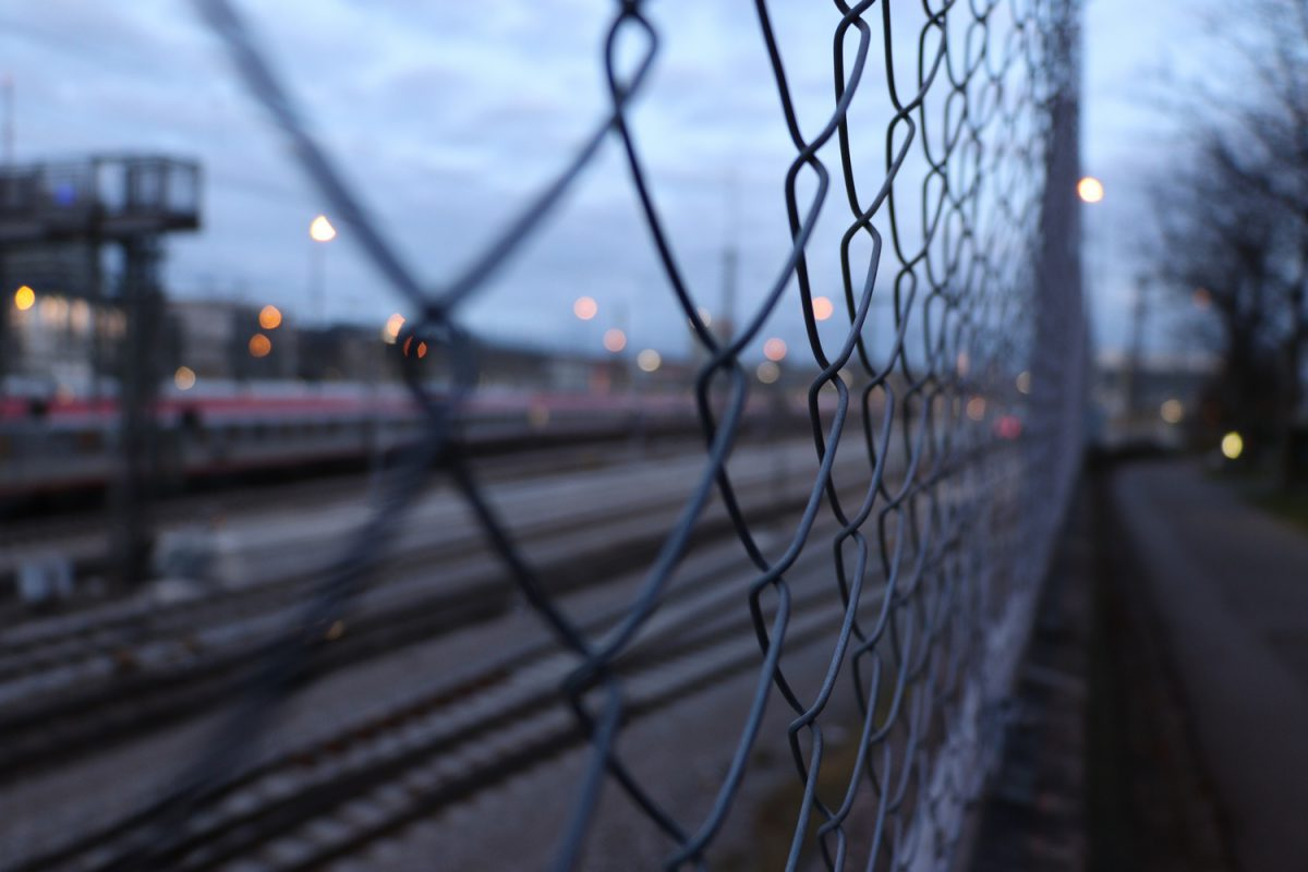 München Zaun mit Blick auf die Gleisanlagen vor dem Hauptbahnhof und den Hauptbahnhof