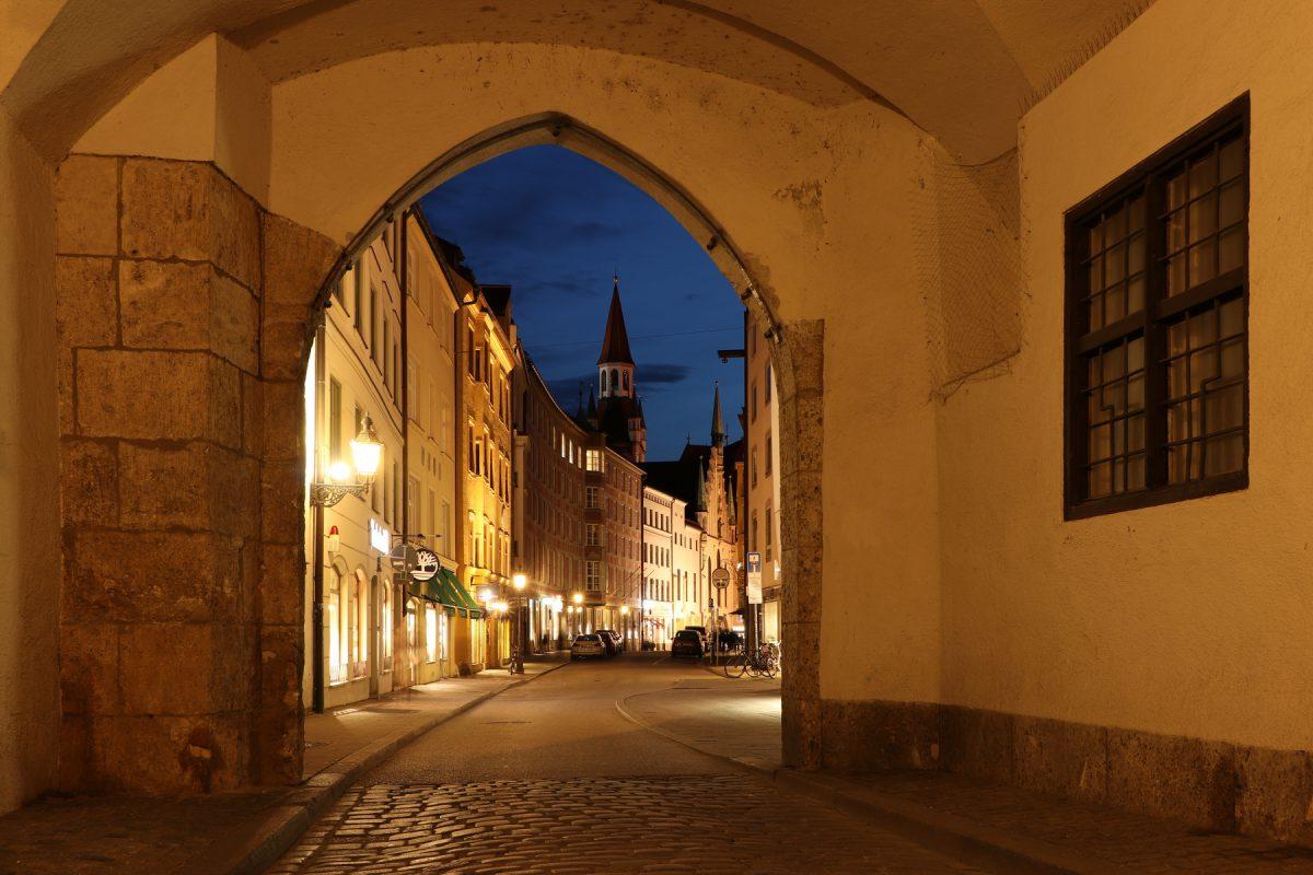 Blick durch ein Tor vom Alten Hof auf das Alte Rathaus und die Burgstraße in München zur Blauen Stunde