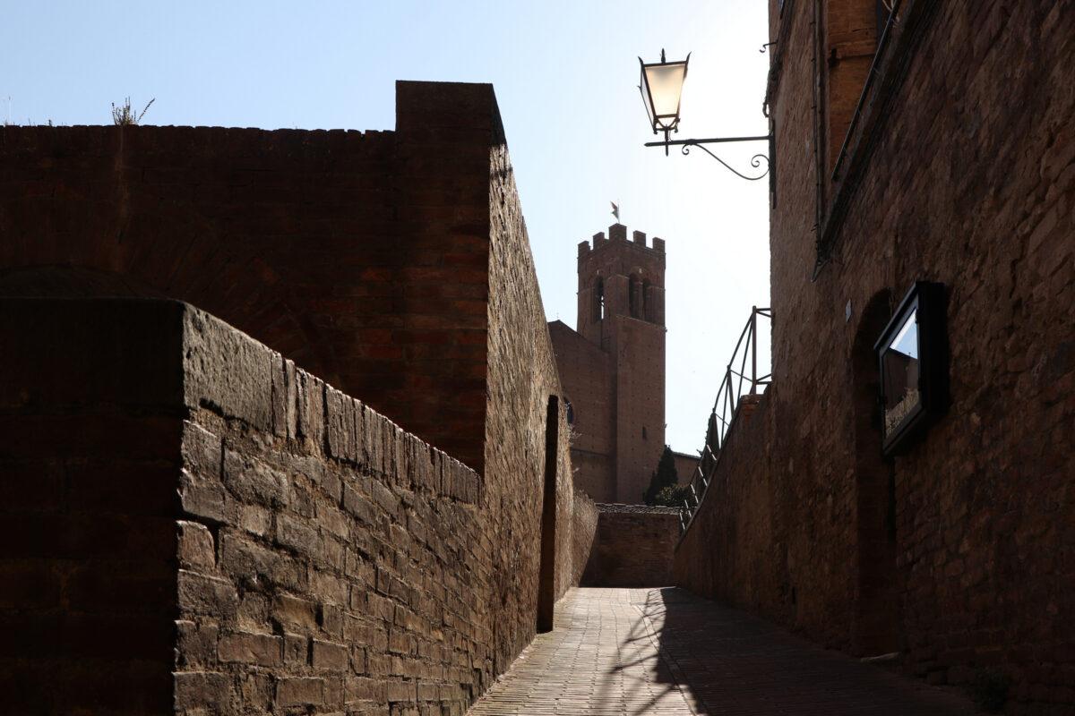 Gasse in der Altstadt von Siena mit Blick auf die Basilica di San Domenico in der Toskana