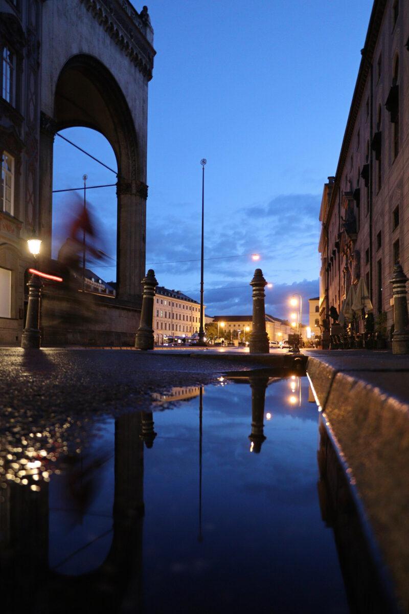 Pfützenspiegelung Blick in Richtung Odeonsplatz in München am Morgen zur Blauen Stunde