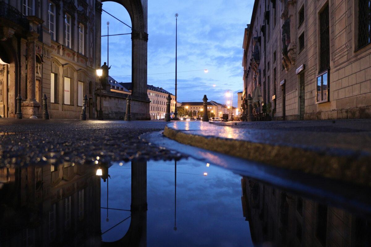 Pfützenspiegelung in der Residenzstraße in München mit Blick auf den Odeonsplatz am Morgen zur Blauen Stunde