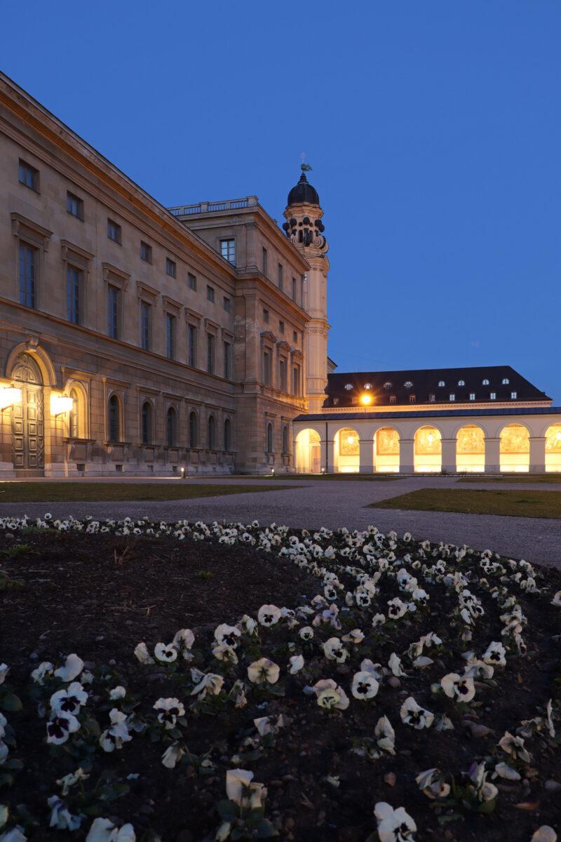 Blumenbeet im Hofgarten in München mit Blick auf die Residenz und die Theatinerkirche zur blauen Stunde