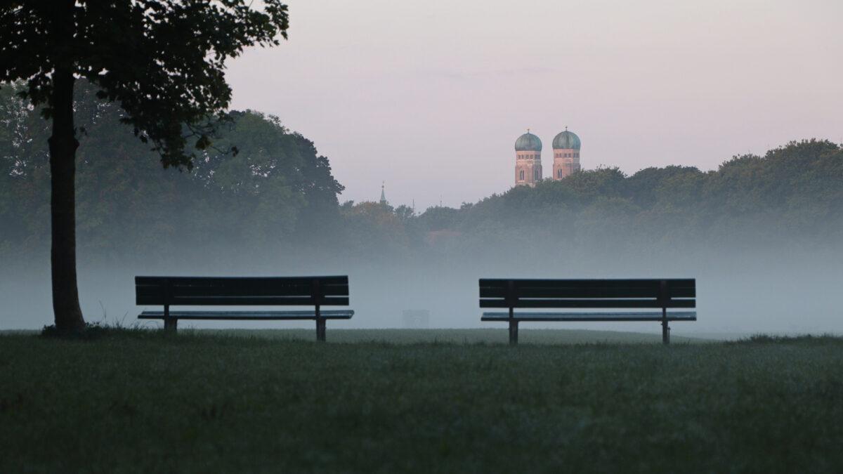 Morgens im Englischen Garten in München mit Blick auf die Frauenkirche bei Nebel
